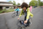 Bicyclists in colorful costumes ride through the Thorpe neighborhood during the annual Hullabaloo bicycle parade Saturday morning.