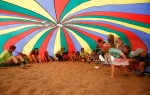 Children and counselors sit under a giant rainbow parachute at the Flagstaff Athletic Club Summer Day Camp Tuesday afternoon.