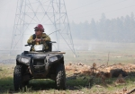 A firefighter with the Coconino National Forest sits near large power lines while monitoring a managed fire operation near Mormon Lake Wednesday afternoon.