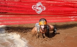 A participant in the Terrain Racing Mud Run Obstacle Race crawls under a barricade through a pit filled with muddy water Saturday.