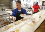 Carolina Medrano lines up trays of sandwiches for students during the lunch hour at Killip Elementary in Flagstaff.
