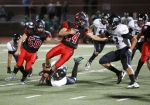 Coconino High School running back Weston Smith (44) holds the ball as the Youngker High defense closes in.