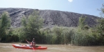 Justin Brown kayaks past a slag pile that contains the remnants of the copper smelting operations that used to be located in the town of Clarkdale. The 20 million-ton pile spills into the Verde River.