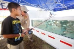 Derian Chatter, 7, sinks a line into a giant fish tank with the help of Steve La Falce at the Trout Unlimited booth at the Coconino County Fair Friday morning. The annual fair continues at the Fort Tuthill County Fair Grounds through Monday.