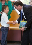 A student from Puente de Hozho School presents Arizona Governor Doug Ducey with a book during the Governors visit to the school Wednesday afternoon.