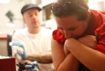 Lerin Cook leans over chair in Birch Avenue Tattoo as artist Pete Meiners prepares to give her a semicolon tattoo as part of Thursday's World Suicide Prevention Day fundraiser at the Tattoo shop.  All proceeds from the event went to help fund the Flagstaff Semicolon Project.