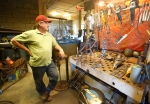 Metal sculpture artist Tom Williams stands in the workshop of his Williams, Ariz. home.