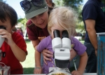 Ella Bundy, 3, looks through a microscope with some help from her mother Elaina Bundy inside the Coconino Community College booth at Science in the Park, which is part of the Flagstaff Festival of Science, Saturday afternoon.