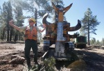 John Magura, Timber Sale Administrator for the Kaibab and Williams District stands next to and explains the operation of a giant feller buncher used to cut down and gather trees. The machine drives up to a tree that is to be harvested and grabs it with large mechanical claws, while a saw blade cuts the tree just above the ground.