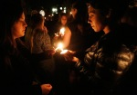 Mourners light candles during a candlelight vigil held at Northern Arizona University Friday night in honor of the victims of a shooting earlier that day that left one student dead and three others in the hospital.