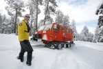 Ken Herron, a long-time volunteer with Coconino County Search and Rescue, stands in front of a snowcat being used to make a trail in the forest below Arizona Snowbowl to help direct backcountry skiers toward the main road.