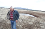 Tom Carter walks past a partially-full cattle tank near his Parks, Ariz. home Friday afternoon. Some residents use the pools of standing water to gauge the state of the shallow water-bearing zones underground that feed many of the domestic wells in the area. These groundwater zones respond quickly to climate events, drying out during periods of drought and recharging with snowmelt or major rainfall.