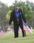 Beverly Thomas of Flagstaff uses a small broom to sweep off the head stones of military services members in preparation for Memorial Day ceremonies to be held at Citizens Cemetery in Flagstaff Monday.