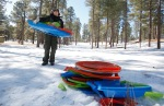 Karen Carswell with the US Forest Service cleans up piles of broken and discarded sleds inside the Fort Valley Experimental Forest which is closed to the public.